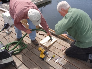 Volunteers install bronze plaques on the docks to acknowldge contributions of supporters.